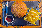 Hamburger with French Fries on a Stone Plate with Eating Utensil