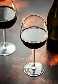 Red wine in a glass, close-up, selective focus. A bottle of red wine and two glasses on the table. Vertical