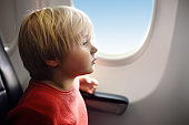 Charming kid traveling by an airplane. Little boy sitting by aircraft window during the flight. Air travel with kids.