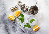 Cocktail shaker and bar tools. Ingredients for a cold alcoholic cocktail. Mojito cocktail. Lemon, mint, ice, rum. Top view, gray background, copy space