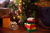 Christmas gift boxes and packages under fir tree at home. Presents near Christmas tree. Eve Xmas.