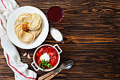 Eastern European food Ukrainian, Russian, Polish. Borscht and Varenyky, Vareniki. Traditional beetroot soup borscht and dumplings with potatoes served with sour cream and parsley on a wooden table