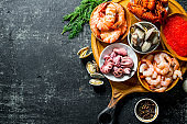 Seafood. Shrimp, crayfish, oysters, octopus and caviar in bowls on the cutting Board.