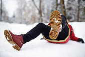 Shot of person during falling in snowy winter park. Woman slip on the icy path, fell and lies.