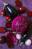 Purple fruits and vegetables on a purple background. Cabbage, apples, purple onions, beets, eggplant. Fresh farm vegetables and fruits in the same color range. Top view. Copy space