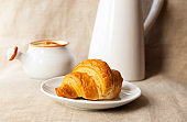 Fresh delicious croissant. Breakfast with croissant, caramel sauce and milk. Close-up. Light background