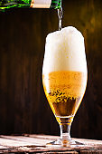 Cold beer is pouring into a glass forming foam.