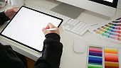 Designer working with digital drawing tablet on studio workplace