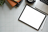 Top view tablet with supplies on designer office desk