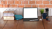 Cropped shot of vintage workspace with blank screen digital tablet and office supplies on wooden table and brick wall