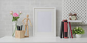 Minimal workplace with mock up frame, books and decorations on white table and grey brick wall