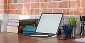 Cropped shot of vintage workspace with blank screen tablet and office supplies on wooden table and brick wall