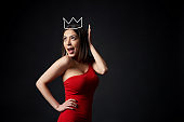 Surprised woman in red dress supporting her crown