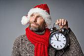 Thinking mature man wearing Santa hat holding big alarm clock looking up
