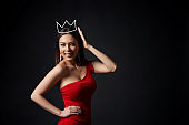 Beautiful woman in red dress supporting her crown