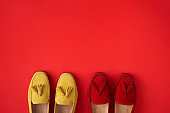 Red suede woman's moccasin shoes over red background