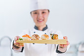 The female chef making the sushi dish