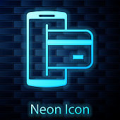 Glowing neon NFC Payment icon isolated on brick wall background. Mobile payment. NFC smartphone concept. Transfer icon. Vector Illustration