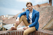 relaxed serious young man in smart casual clothes sits