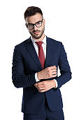 Confident man adjusting his sleeve while wearing sunglasses