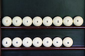white balls for playing Russian Billiards, located on the shelf in order