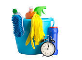 in a blue bucket, multi-colored bottles, a brush and yellow rubber gloves are lying, for cleaning surfaces, on a white background, with space for an inscription, next to it is a bank with powder and time on the alarm clock