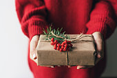 Elegant female hands holding a gift box decorated with red berries.