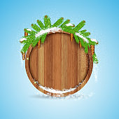 round wood border with snowy fir tree branch and cones on blue background