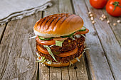 Double vegetarian Burger with falafel Patty and vegetables on old wooden table