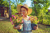 Young woman female farmer happy smiling carry two pots with flowers by her house yard garden flower pot taking care of the plants wearing hat and summer dress