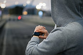 Woman athlete using smart watch activity tracker time and gps during running training.