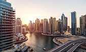 Aerial view of cityscape and skyscraper at sunset in Dubai Marina.