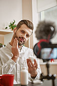 Soft skin. Vertical photo of positive male beauty blogger applying cosmetic cream on his face while live streaming.