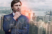 Thinking about business. Handsome bearded businessman touching his chin and looking away while standing against of cityscape background
