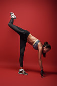 Good, better, best. Sportswoman standing over red background, stretching her body