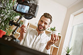 Online shopping. Cheerful young male blogger recording new video blog episode about new cosmetic products.