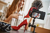 Online shopping. Pretty and young blogger showing her red high heel shoes online to her subscribers