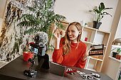 So easy to be perfect! Cheerful and young blogger presenting a makeup palette on camera while recording new video tutorial for social media