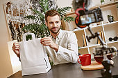 Online shopping. Handsome male blogger holding paper shopping bag and looking at camera while live streaming