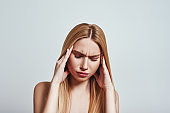 Terrible pain. Frustrated young woman touching a head with hands while standing in studio on a grey background. Pain concept