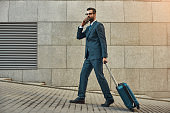 Always in touch. Side view of handsome bearded man in suit pulling his luggage and talking by phone with client while walking outdoors