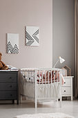 Vertical view of white crib with pastel pink bedding and cotton balls in grey and beige fashionable baby bedroom