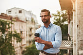 Relaxing after work. Young and handsome bearded man in eyeglasses and formal wear holding cup of coffee and looking away while standing at the office balcony
