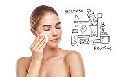 Your daily skincare routine. Portrait of pretty young woman removing makeup from her face with cotton pad while standing against white background with hand drawn skin care set on it.