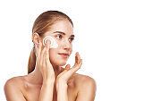 Perfect skin. Beautiful young woman applying cosmetic cream on her face while standing against white background. Beauty products