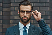 Smart and successful. Confident businessman in formal wear adjusting his eyeglasses and looking at camera while standing against brick wall