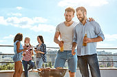 Enjoying barbeque together. Two smiling young men drinking beer and barbecuing meat on the grill while standing on the roof with friends.