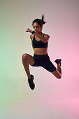 Never Stop Moving! Full length of young athlete woman with perfect body in sports clothing jumping in studio against colorful background