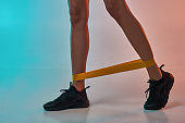Cropped photo of woman doing exercises with resistance band while standing in studio against colorful background