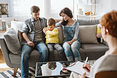 Caring parents and misbehaving boy during therapy session with counselor